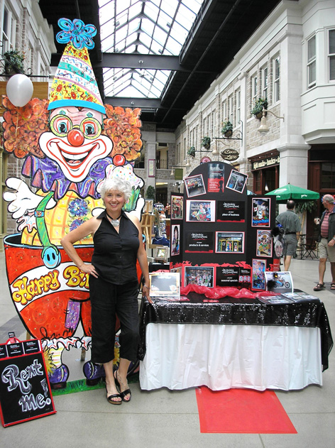 Dorothy Amey posing in front of Drawing Attention booth for Art in the Street in Guelph.