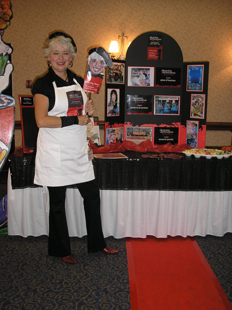Dorothy Amey in front of Drawing Attention booth at a business trade show.